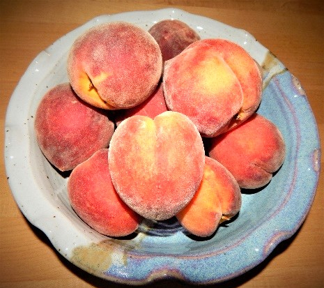 Bowl with whole raw peaches